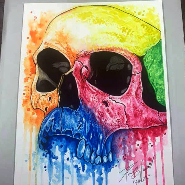 illustration of a skull filled in with dripping colors of watercolor paint